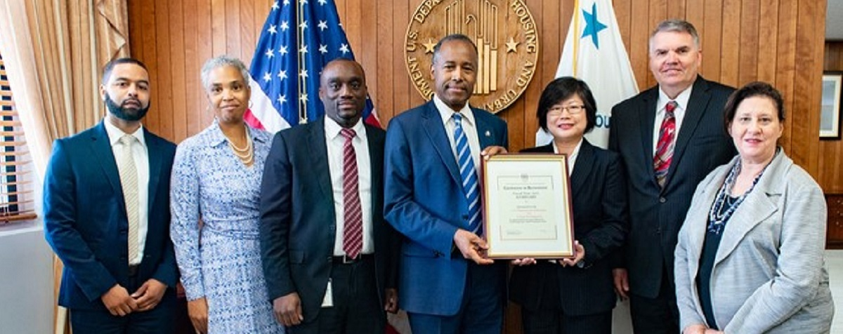 Secretary Carson displays certificate with members of OSDBU, procurement and program offices.