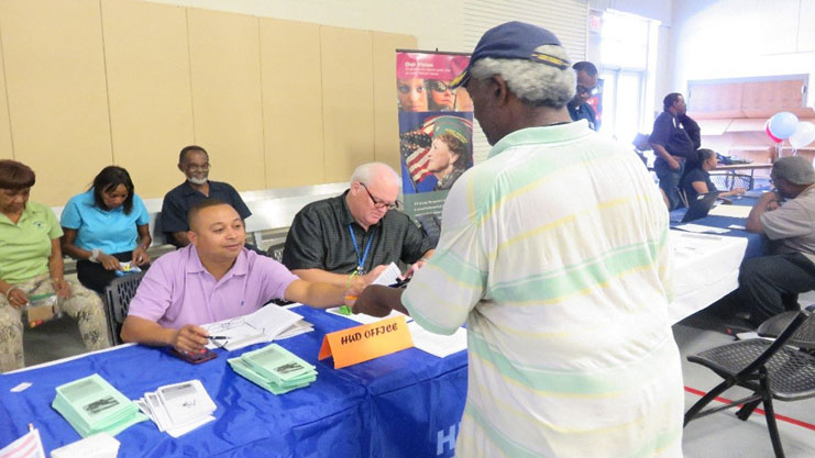 [Public housing revitalization specialists Anthony McIntyre and Craig Wood assist a homeless veteran with information on VASH vouchers.]. HUD Photo