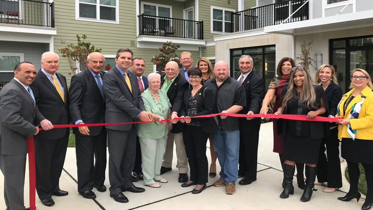 [HUD RA Lynne Patton; Christiana Foglio, CEO of Community Investment Strategies; Thomas A. Arnone, Monmouth County Freeholder Director; Anthony Marchetta, Executive Director of NJHMFA; Anthony P. Fiore, Deputy Mayor of Middletown; Raoul Moore, Senior Vice President, Enterprise Community Partners; tenants and friends cut the ribbon at the grand opening of Bayshore Village Apartments]. HUD Photo