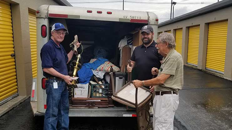[HUD staff Tom Ryan and David Railey help Peter Seely load his belongings onto the moving truck].  HUD Photo