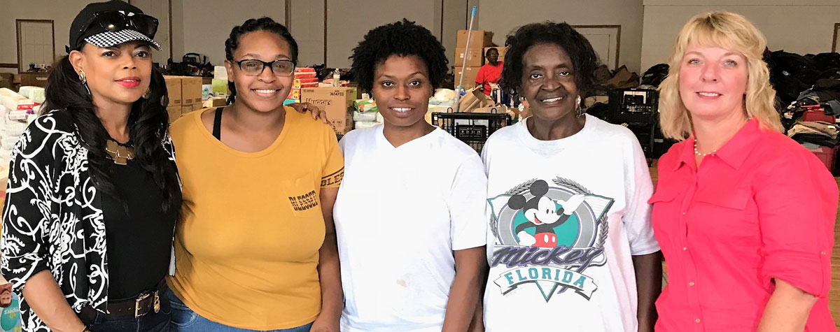 [Far left - HUD SE Regional Administrator Denise Cleveland-Leggett with three Hurricane Florence survivors at the New Bern Disaster Clothing Distribution Center with Jody Moses, HUD NC Field Office Director on the far right]. HUD Photo