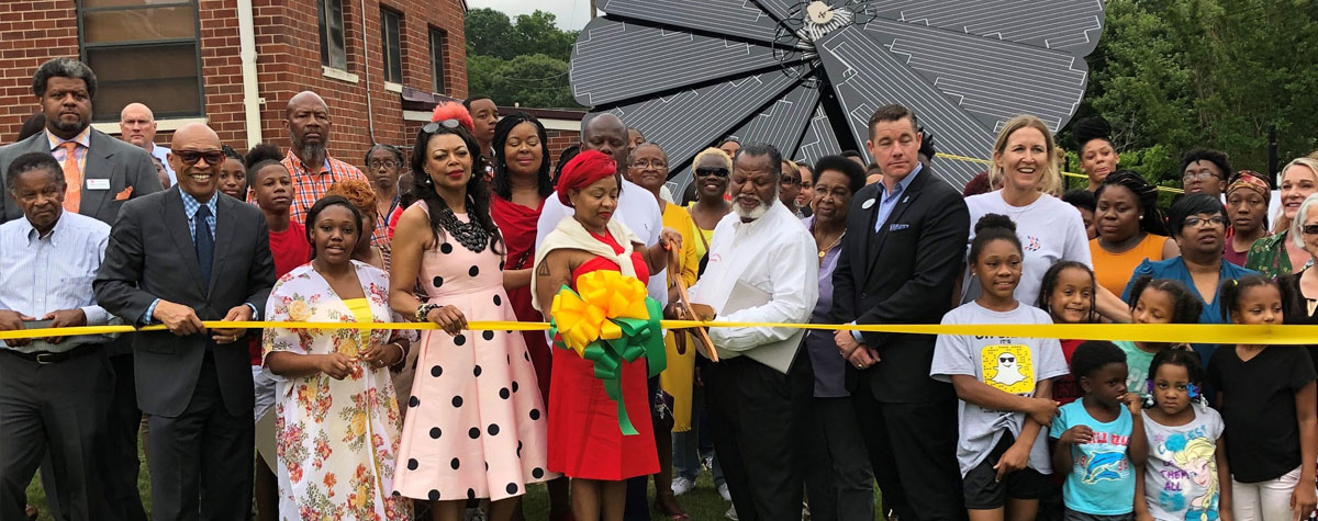 [HUD SE Regional Administrator Denise Cleveland-Leggett (fourth from left) along with community leaders, residents and children participate in the ribbon cutting ceremony for the new solar energy array for the LaGrange Housing Authority residents].