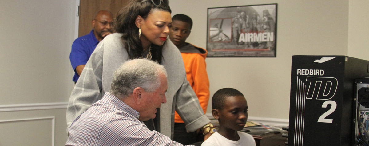 [Crispin Ntwari, middle school resident, receives flight simulator training as part of the Housing Authority of Bowling Green's STEM and Aviation initiative with an flight instructor volunteer and Denise Cleveland-Leggett, HUD SE Regional Administrator looking on.]. HUD Photo