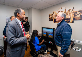 [Student resident receives hands on flight simulator training as Secretary Carson is updated on the innovative program with a volunteer flight instructor.]