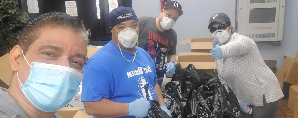 [Four Volunteers wearing face masks from the Taino Towers EnVision Center prepare meals in black plastic bags to hand out to the East Harlem, NY community]. HUD Photo