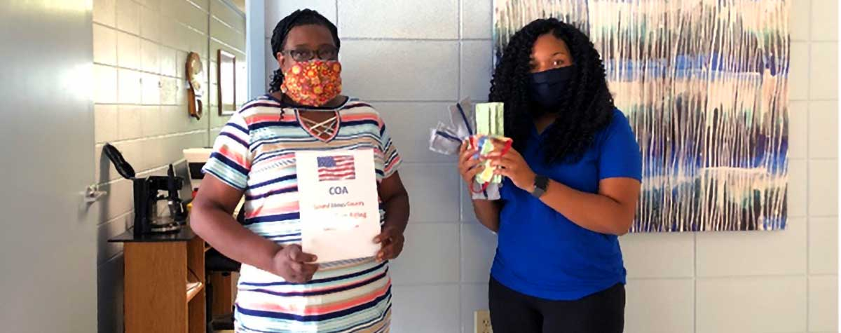 [Margaret Jones, representative of Council on Aging and Tramel McMillan, Laurel Housing Authority  property manager prepare to distribute masks]. HUD Photo