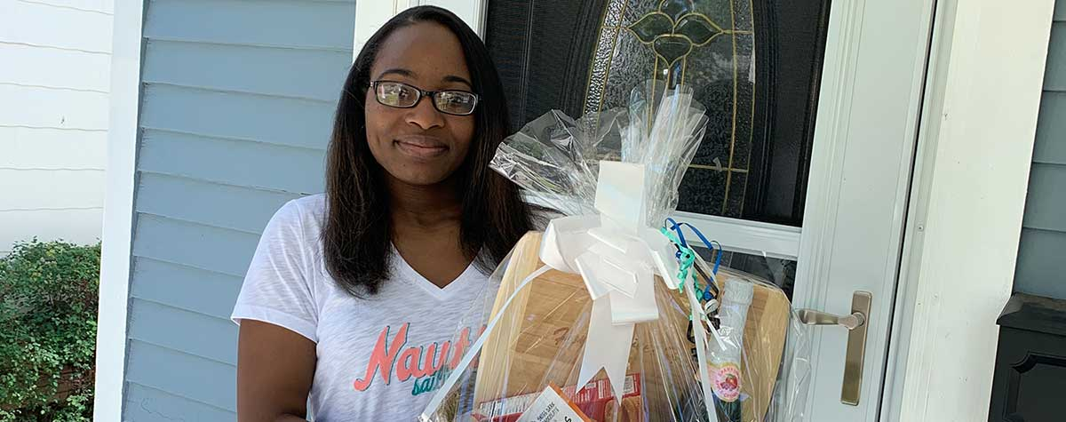 [Ashley Sims standing by the front door of her new home with a gift basket from the Rochester Housing Authority]. HUD Photo