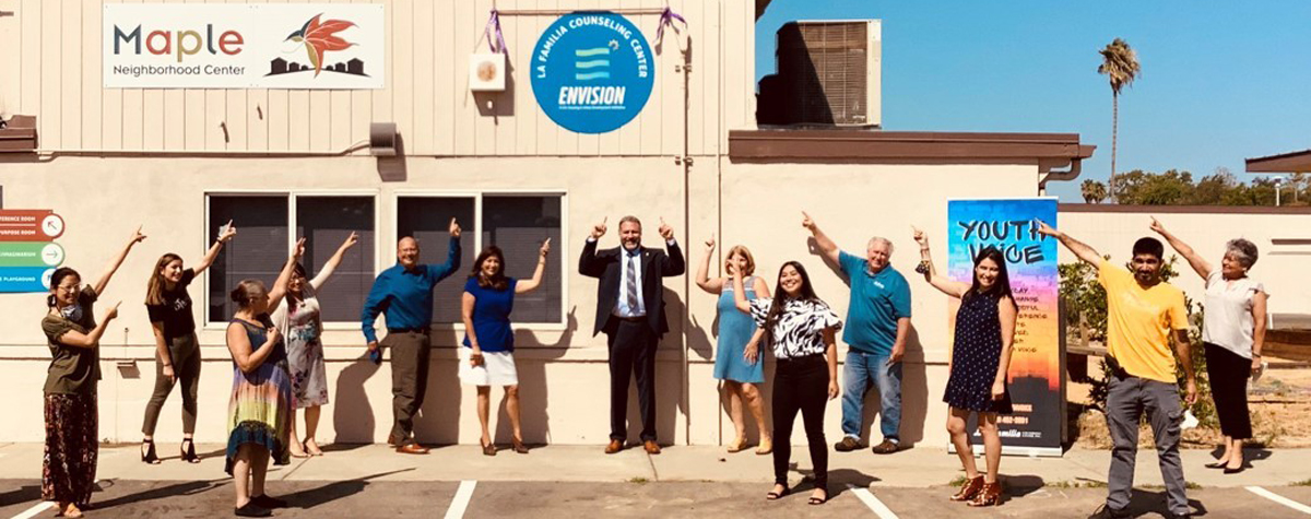 [Photo: Excited people pointing at new EnVision Center sign on building]. Staff Photo
