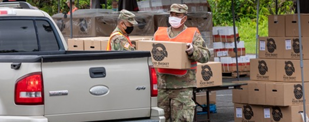 [Photo: A member of the National Guard loads a food box onto a resident's truck].