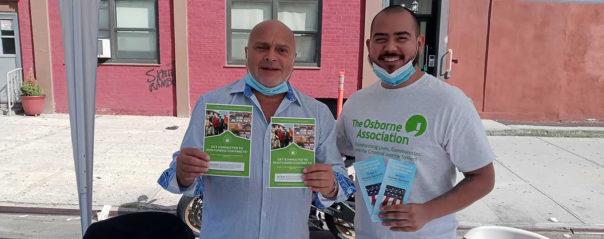 [Two volunteers hold up HUD Section 3 Program materials]. HUD Photo