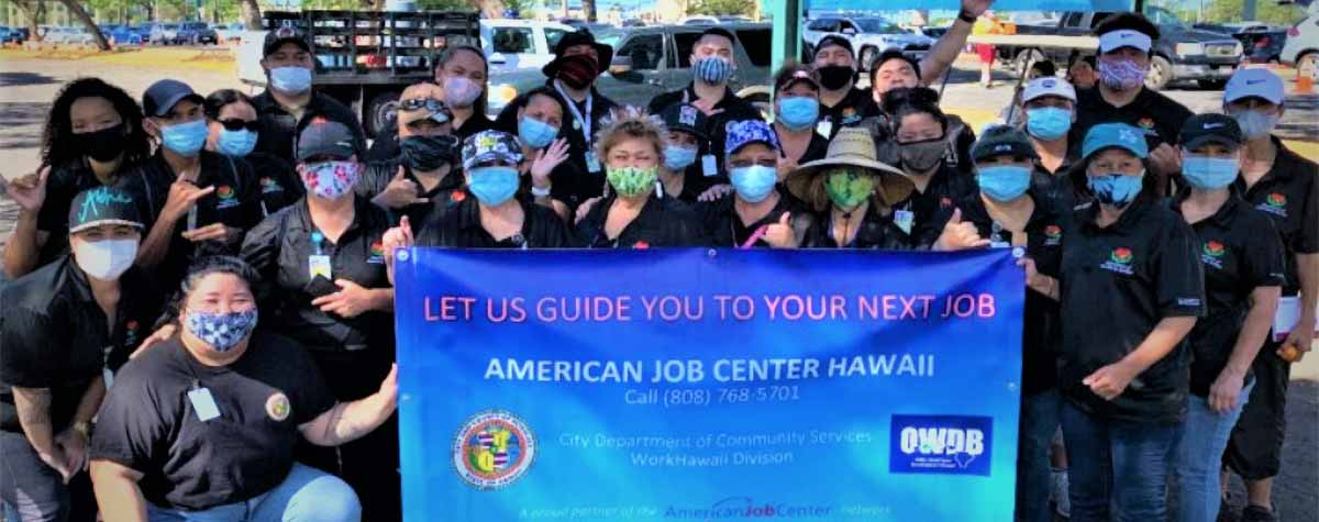 [Photo: T.E.A.M. Work Hawaii, holding banner, provides next job outreach services in response to COVID-19]. HUD Photo