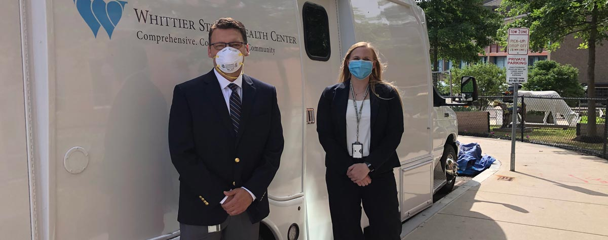 [HUD R1 Deputy Regional Administrator Rob Forti and Maine State Director Kelsey Brown stand by the Whittier Street Health Center's mobile health clinic van]. HUD Photo