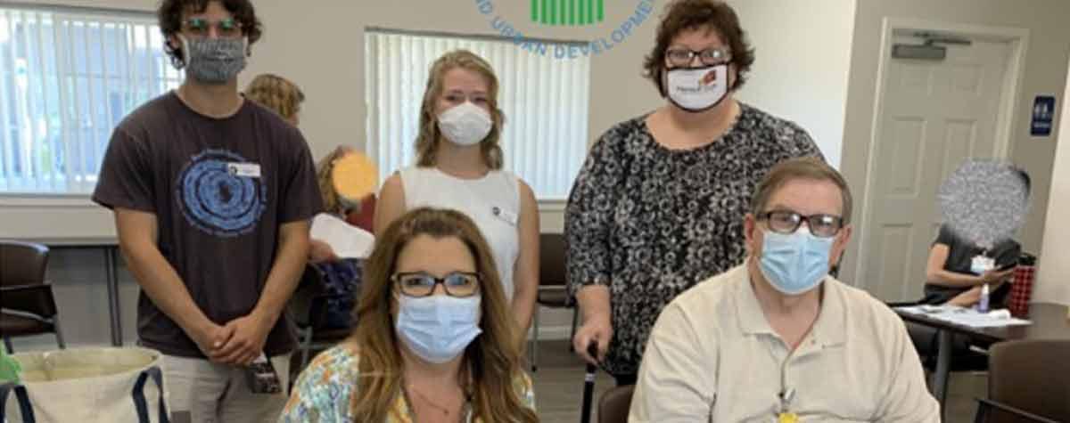 [Blake Matthews (VISTA member), Amber Nichols (VISTA Member), Patti Webster (HomeFront Ex. Director); Bottom left to right: Brenda Koch (RiverStone Health), Gregory Neill (RiverStone Health)]. HUD Photo