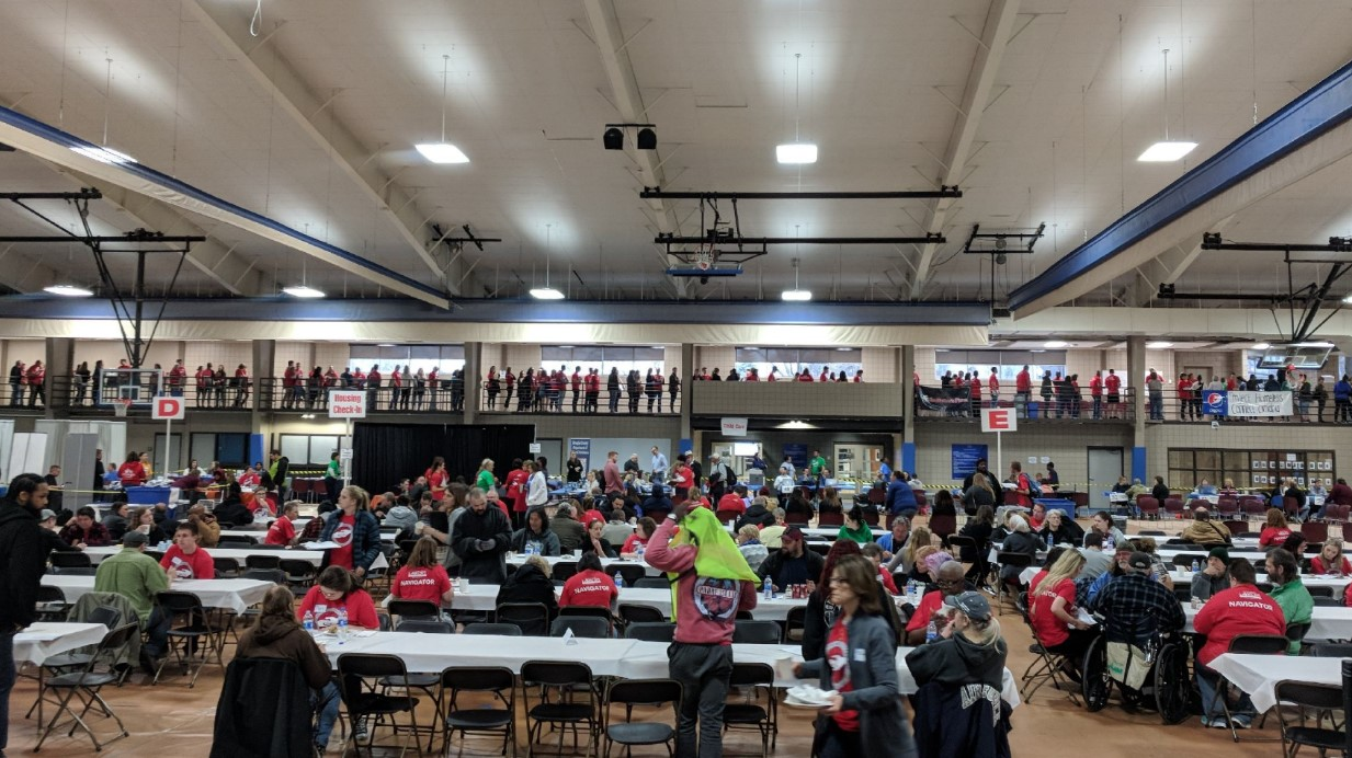 [People assisting homeless at tables with others waiting in the background.].
