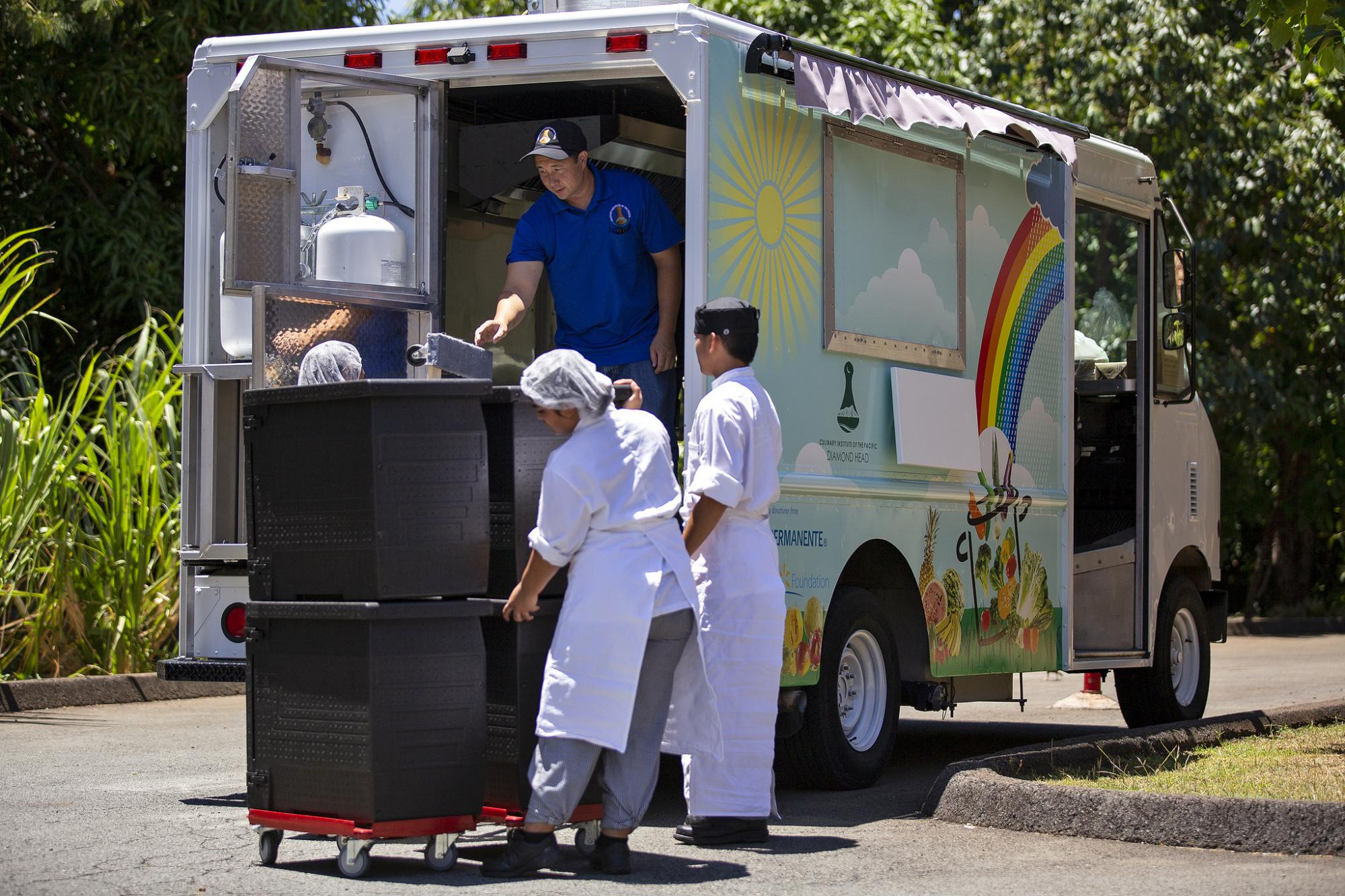 people unloading containers from food truck