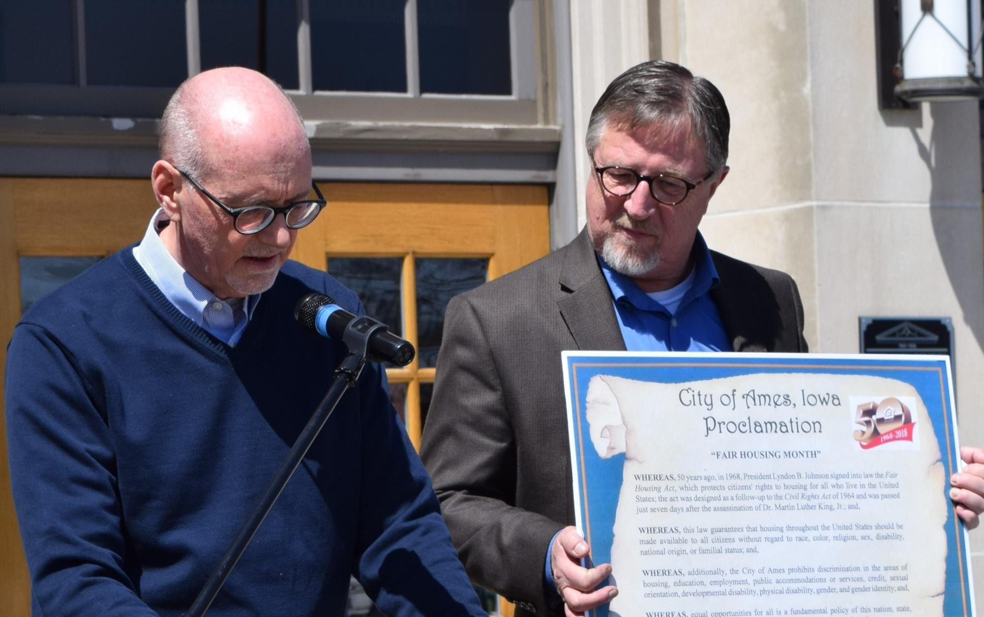 [Mayor Haila reads the Proclamation while Field Office Director Eggleston holds a life size version of the proclamation].