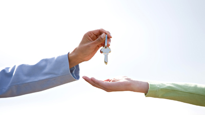 handing keys over to another person's hand. HUD Photo
