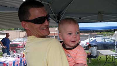 [A father whose family lives in Kingsport public housing shares quality time with his young son during annual Father's Day Event]. Photo courtesy of Kingsport Housing Authority