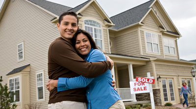 Happy couple in front of house with sold sign. HUD Photo