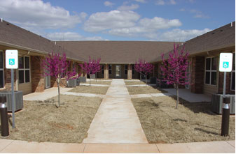 Single story apartments with grass in courtyard . HUD Photo