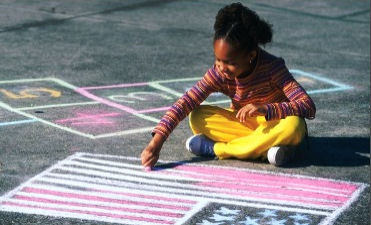 Image of a child drawing with chalk.