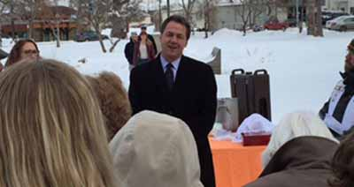 Governor Steve Bullock provides remarks at the ceremony, snow and trees in background