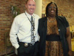 [Photo 1: Officer John Kikkert and Phyllis Hargrove in front of brick wall]