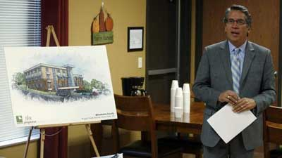 Regional Administrator Rick Garcia next to easel holding sketch of proposed building.